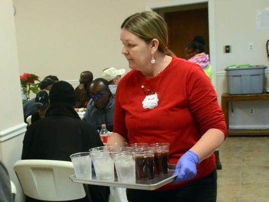 Marie Hulsey of Jena serves drinks at the Salvation Army's Christmas dinner Thursday. Hulsey and members of her card group volunteered to help serve.