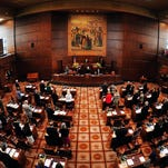 Members bow their heads in prayer at the Senate during the first day of the 2015 Oregon Legislature at the state Capitol building on Jan. 12.