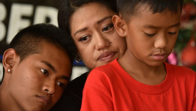 Mika Piolo, widow of the late Guam Police Department Sgt. Elbert Piolo, becomes tearful while talking about how she learned of his death during an interview at a Piolo home on Jan. 2. With her are two of their four children, Jaden, 14, and Zaven, 10.