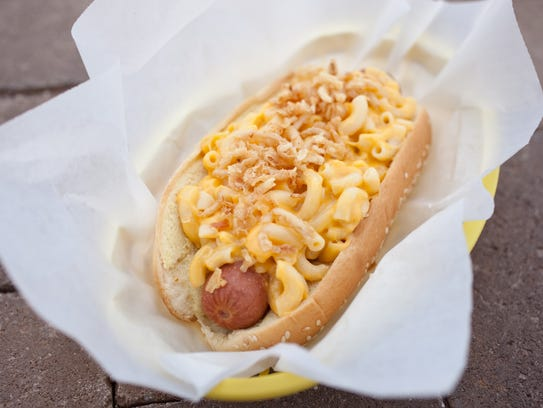 A hot dog covered in macaroni and cheese and crispy