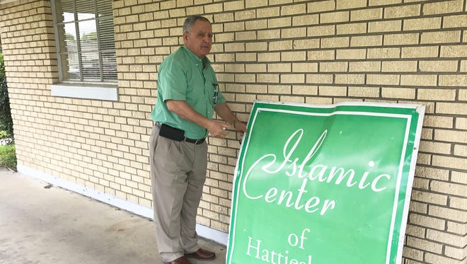 Jerry Buti shows the sign vandalized at the Islamic Center of Hattiesburg.