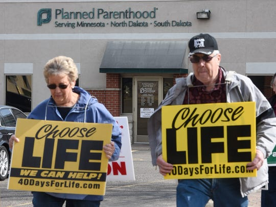 Protestors hold signs Saturday, April 8, outside the Planned Parenthood clinic in St. Cloud.