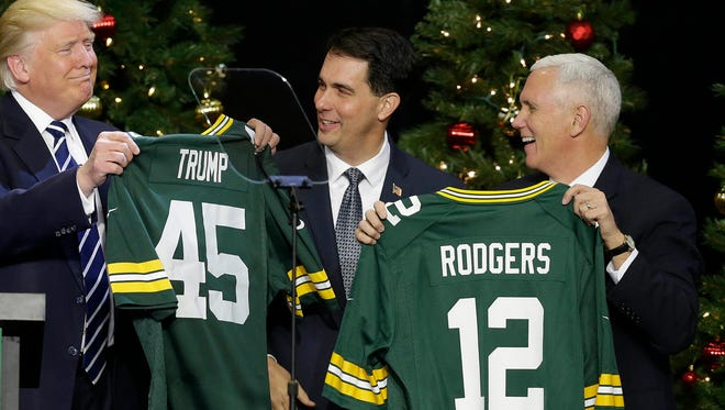 President-elect Donald J. Trump and Vice President-elect Mike Pence accept Packers jerseys from Gov. Scott Walker (center) and House Speaker Paul Ryan (not pictured) after Trump spoke to supporters Tuesday night at the Wisconsin State Fair Exposition Center.