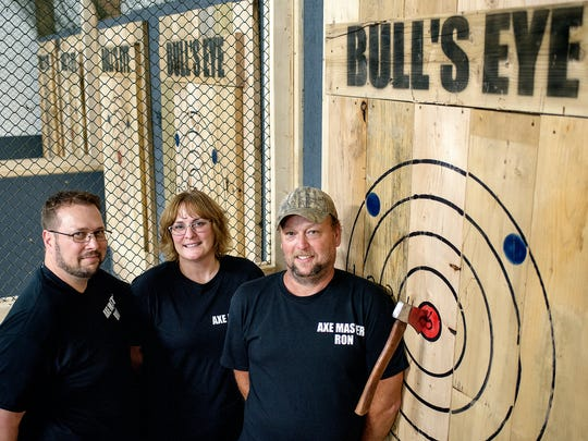 From left, owners Rich Baker, his wife Jennifer, and Ron Bushard, photographed on Friday, July 13, 2018, opened the Bull's Eye Axe Throwing business in Lansing.