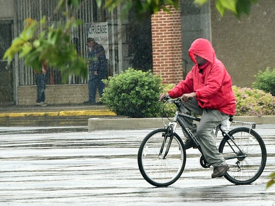 A man rides his bicycle through a rain-soaked parking lot at Southgate Shopping Center, Chambersburg, during a storm Tuesday. Temperatures will return to 80 degrees later this week.