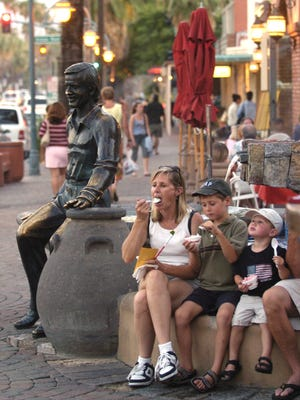 A family has ice cream in the old Plaza area of downtown Palm Springs seated at the Sonny Bono fountain.