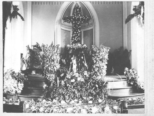 """An Italian itinerant artist, Samuel Alberti, did the fresco on the wall of the Universalist Church's audience room. The seemingly recessed alcove is an optical illusion called """"trompe d'oeil."""" The altar is decorated for some special occasion."""