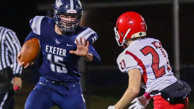 Exeter quarterback Jonathan Bunnell fends off Spaulding's Hunter Baker during Friday's Division I football game in Exeter.