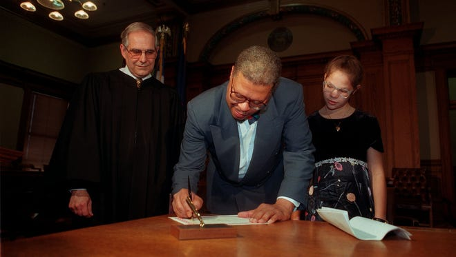 Stuart Dunnings III signs to make his swearing-in as Ingham County prosecutor official on Dec. 29, 1996. Judge Peter Houk and Dunnings' daughter, Coral, look on.