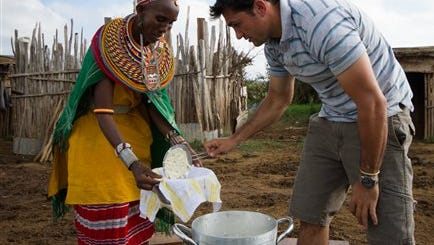 """In this photo made available by production company Quite Bright Films, chef Kiran Jethwa, right, makes ricotta cheese with a Samburu tribeswoman, during the filming of an episode of the series """"Tales from the Bush Larder"""", in Maralal, Kenya."""