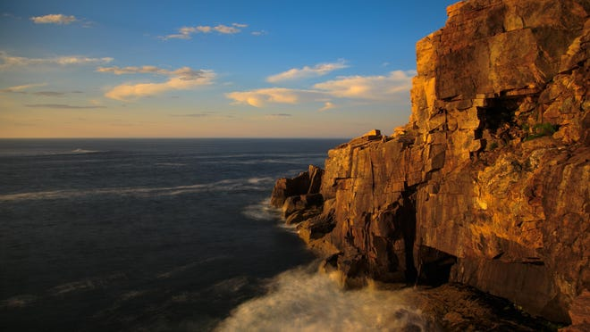 """Sunrise turns Otter Cliff and the Atlantic spray pink along Ocean Drive at Acadia National Park. With the park located so far east, it has been dubbed the home of """"America's first sunrise."""""""