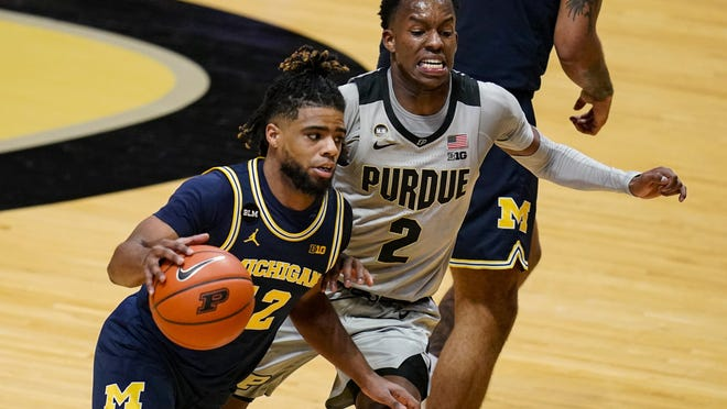 Michigan guard Mike Smith (12) drives on Purdue guard Eric Hunter Jr. (2) during the second half of an NCAA college basketball game in West Lafayette, Ind., Friday, Jan. 22, 2021. Michigan defeated Purdue 70-53.