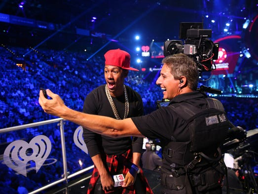TV personality Nick Cannon, left, poses onstage during