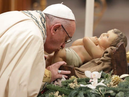 Pope Francis kisses a statue of the Divine Infant as he celebrates a new year's eve vespers Mass in St. Peter's Basilica at the Vatican, Saturday, Dec. 31, 2016.
