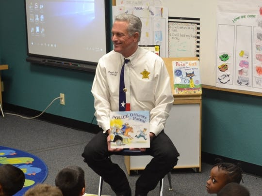 Sheriff David Jones reads to  Stacey Miles and Sandra