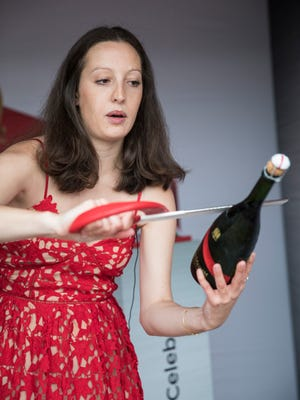 Julia Jeanselme, with G.H. Mumm Champagne, uses a saber to uncork a bottle of champagne on Thurby. May 4, 2017.