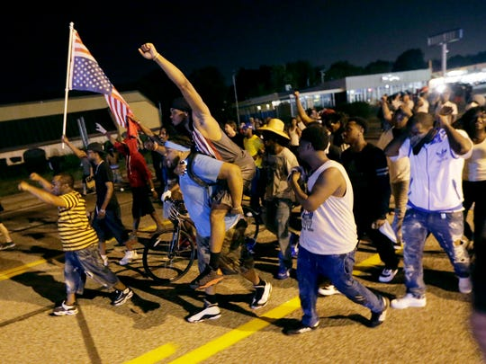 People march down the street after a standoff with police Monday, during a protest for Michael Brown, who was killed by a police officer Aug. 9 in Ferguson, Mo.