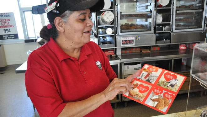 Alicia Janas at KFC in Abilene shows the scratch-and-sniff Valentine's Day cards the fast food restaurant had available on Wednesday.