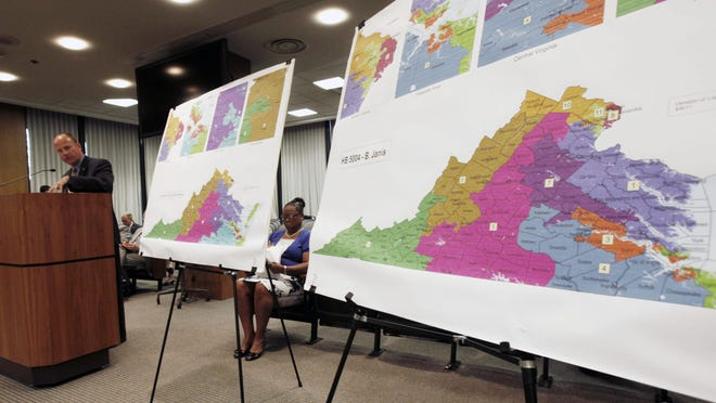 Then-Del. William R. Janis, R-Henrico, at podium, presents his congressional redistricting plan to the Senate Privileges and Elections committee at the General Assembly Building in Richmond in 2011, as state Sen. Mamie E. Locke, D-Hampton, who presented her own plan, sits between the two maps.