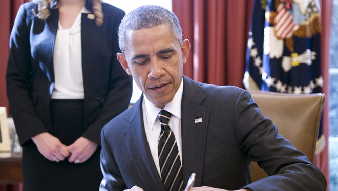President Obama signs an Executive Order on greenhouse gas emissions in the Oval Office on March 19, 2015.