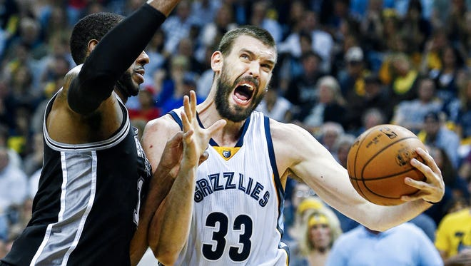 Memphis Grizzlies center Marc Gasol (right) drives the lane against San Antonio Spurs defender LaMarcus Aldridge (left) during second quarter action in the sixth game of their NBA first round playoff series at the FedExForum.