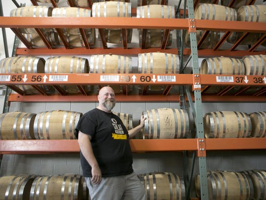 Owner Brian Cummins poses next to the barrels where the company ages Great Northern Distilling's spirits in Plover.