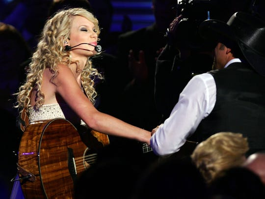 Taylor Swift shakes hands with Tim McGraw during the 42nd annual ACM Awards in 2007.
