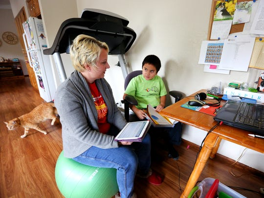 Fourth grader Josiah Bumanlag completes his Oregon Connections Academy language arts school work as his mother Heidi Bumanlag supervises at their home, Friday, October 16, 2015, in Salem, Ore.