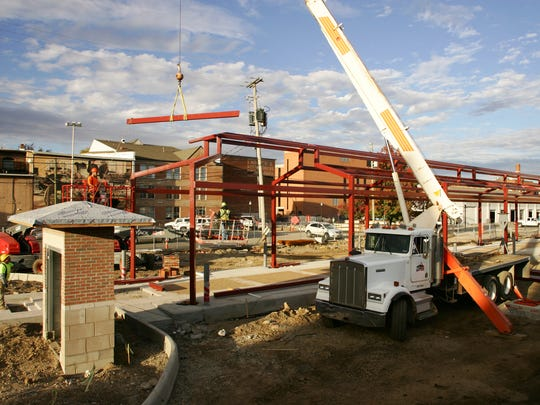 Construction workers lower beams into place Monday afternoon for the Canal Market District farmer's market in downtown Newark.