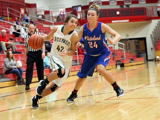 Greenwood's Alex Kincaid drives by Whiteland's Ashley West in Saturday's Johnson County tournament final.