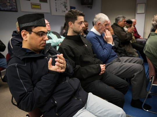 People pray during a moment of silence for San Bernardino victims at Baitun Naseer Mosque on Saturday, December 19, 2015.
