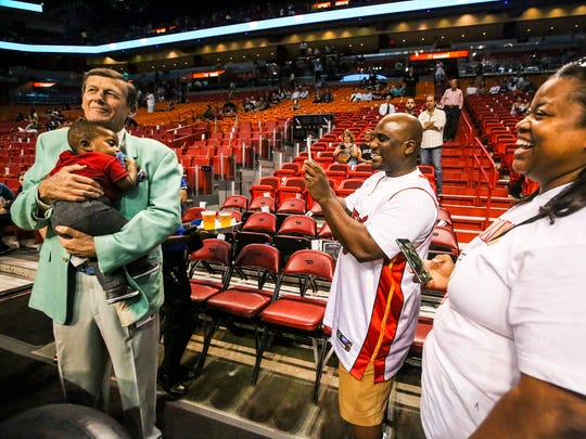 """Craig holds a child as his parents take photos. Craig kept the baby for a while, """"you know you have to give the baby back right"""", it's mother said. Craig Sager, the eccentric TNT/TBS NBA sideline reporter began his broadcast career with WINK-TV in Fort Myers in the mid-1970s. HeÕs now renewing his very public battle against leukemia while still working NBA games. He worked the Chicago Bulls at Miami Heat game on Thursday, April 7, 2016."""