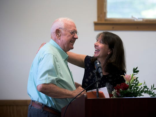 Millville principal Kathleen Procopio receives flowers from club member George Mitchell as he speaks of her retirement during a Kiwanis luncheon honoring Millville's top ten academics at the Thunderbolt Club Thursday, June 2 in Millville.