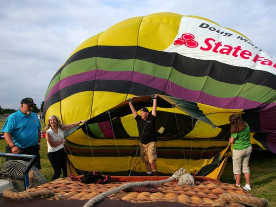 Sponsor Doug Marmie, center, holds open the base of a balloon as pilot Sean Askren, left, prepares to fill the balloon with hot air prior to liftoff Friday during the balloon festival at the fairgrounds.
