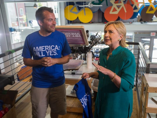 RAYGUN owner Mike Draper gives a tour of his shop to Democratic Presidential nominee Hillary Clinton in Des Moines, Wednesday, Aug. 10, 2016.