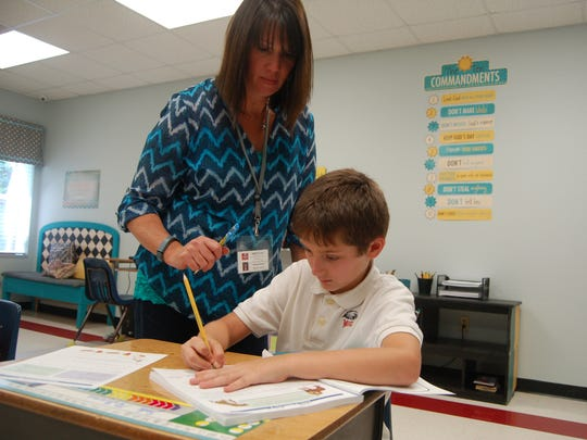 Holly Solomon teaches Zeke McGinnis, an 8-year-old third-grader, how to write the correct form of a sentence in cursive Thursday at the Mountain Home Christian Academy. At the Christian Academy, staff said students are taught respect.