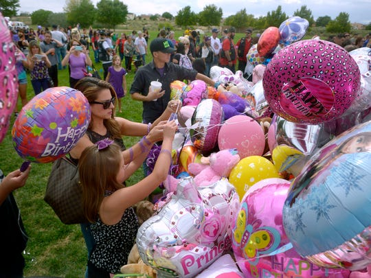 In a Sunday, Aug. 28, 2016 photo, Stephanie Duneman and her daughter Isabella Duneman, 9, tie up balloons they brought to celebrate the birthday of Victoria Martens in Mariposa Basin Park, in Albuquerque. Ten-year-old Victoria Martens was brutally slain last Wednesday.