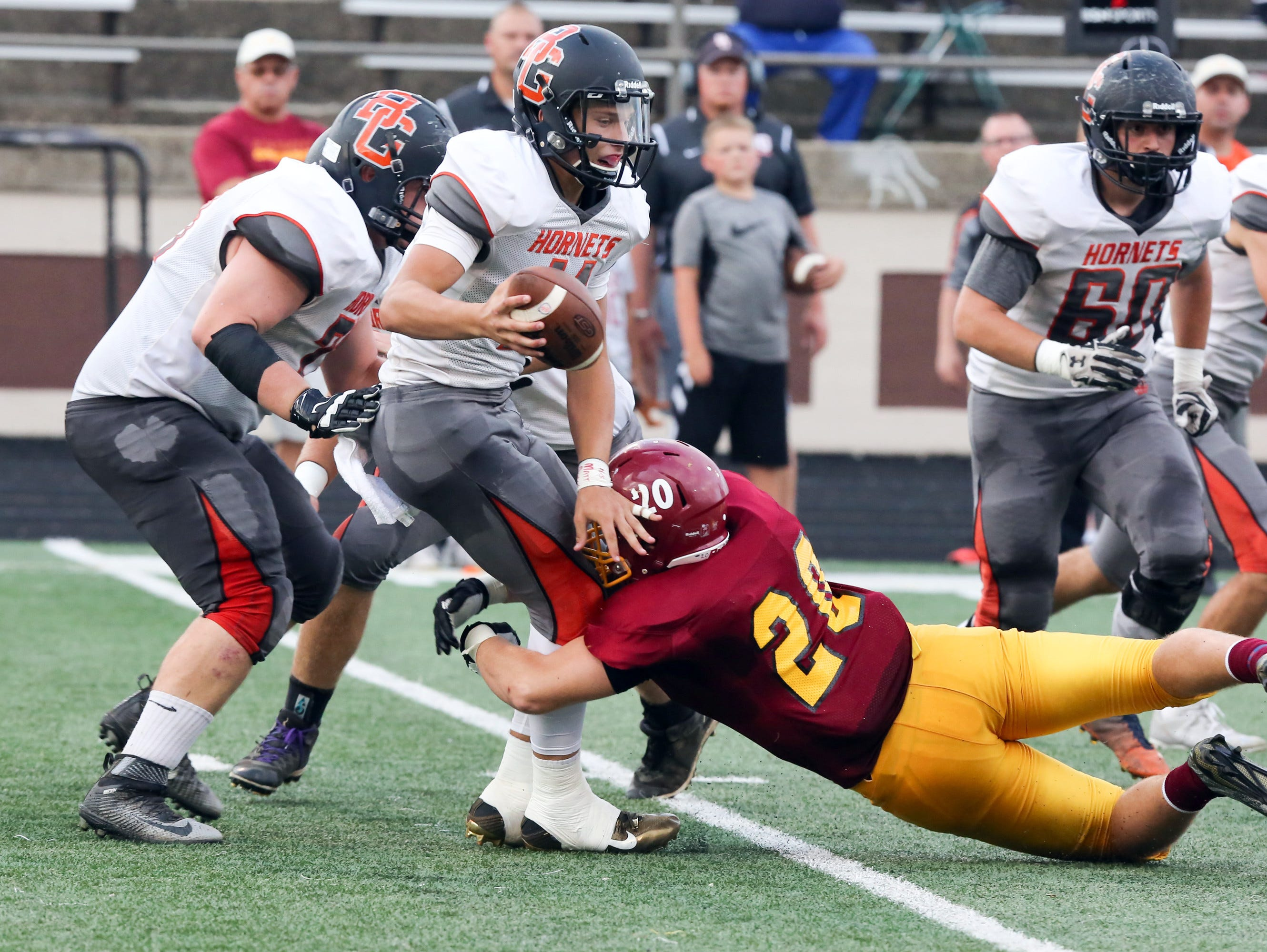 Scecina's Collin Connor wraps up Beech Grove QB Chase Andries Friday night.