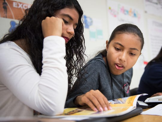 Shadia Manzur, who moved to Berea from Columbia six weeks ago, helps Ericka Jahaira Lobo, who moved from Honduras three weeks ago, read a book in english during a newcomers program at Berea High School on Thursday, October 20, 2016.