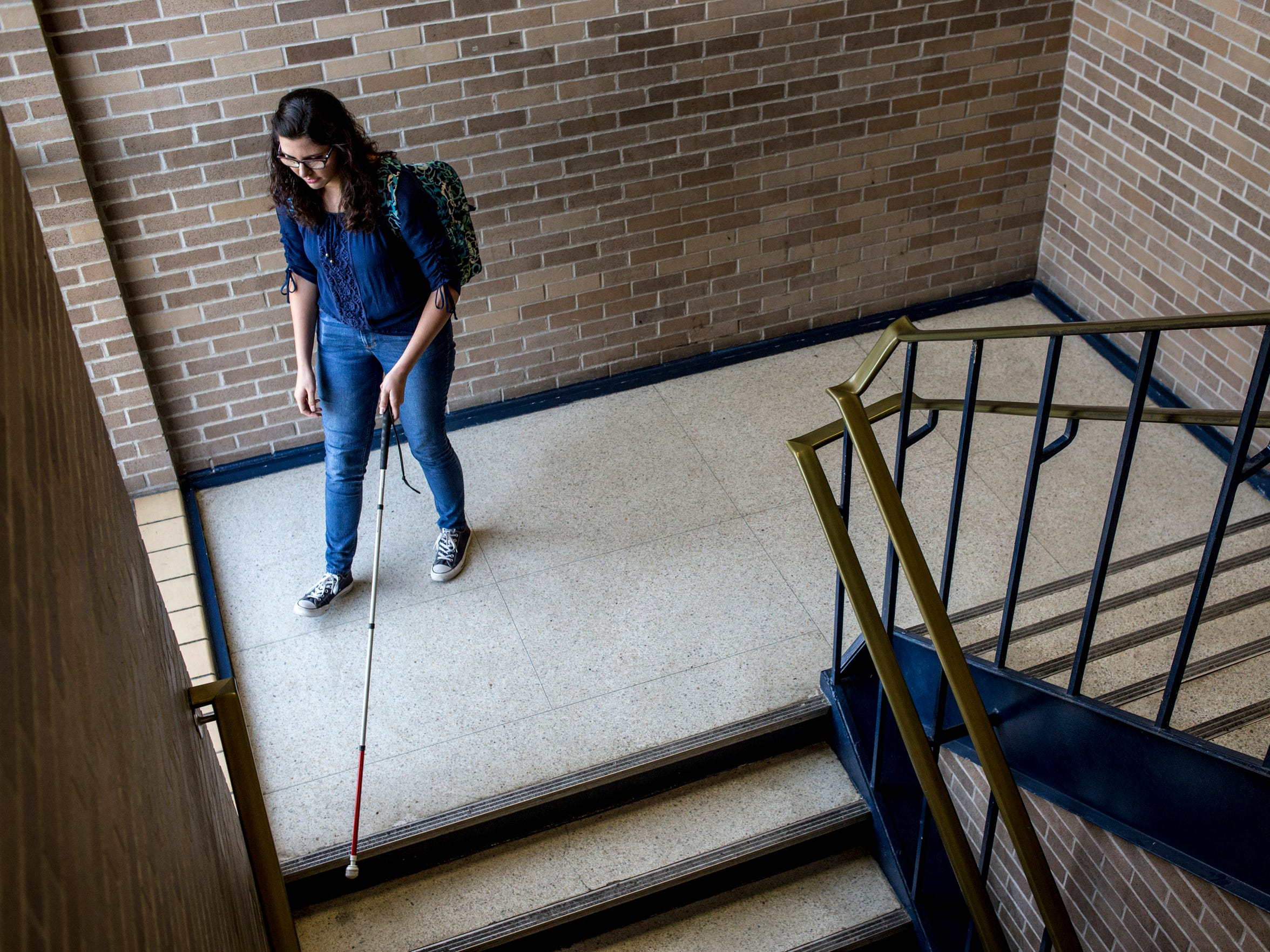 Alexandra Allers, 16, uses a cane to navigate down a stairwell between classes Nov. 18, 2016 at Port Huron Northern High School.