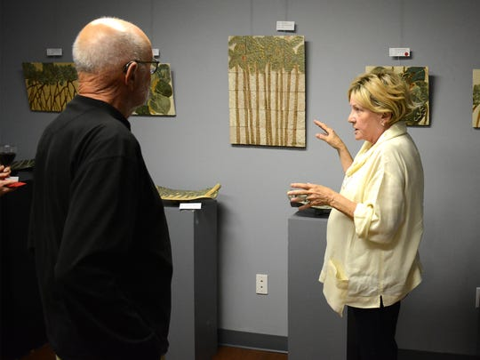 "In La Petite Galerie, exhibitor Sandy Ward Howe discusses her works with fellow artist Donald Sunshine. The Marco Island Center for the Arts held a reception Tuesday evening for an exhibit of paintings by Betsy Ross Koller, showcasing her ""naive"" interpretations of rustic scenes, many of them snowscapes, at their gallery on Winterberry Drive."