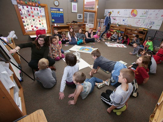 Katie Keller, far left, conducts a philanthropy project during class at Community Montessori, a charter school in New Albany.  The students were helping to collect loose change to send to an impoverished school in Nepal. Jan. 12, 2017
