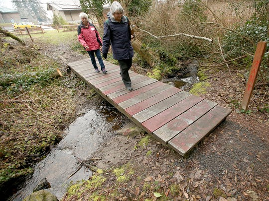 Volunteers cross a small footbridge as they enter the trail system behind the Village Green Community Center in Kingston during a previous point in time county in Kitsap County.