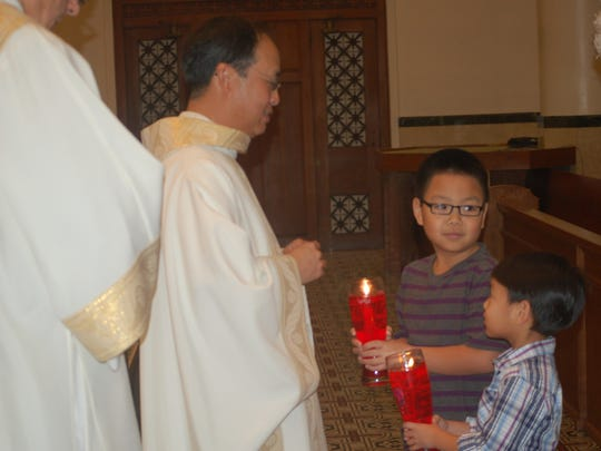 The Rev. Hanh Van Pham (left) accepts the gifts from his nephews, Brayden Tran (center) and Kayden Tran during a Mass of thanksgiving celebrating the 25th anniversary of Pham's ordination to the priesthood Jan. 20, 2017, at Corpus Christi Cathedral.