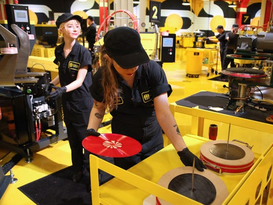 Katie Lass of Hamtramck, left, and Alejandra Villegas of Detroit produce limited-edition vinyl records during the opening of Third Man Pressing in Detroit on Saturday, Feb. 25, 2017.