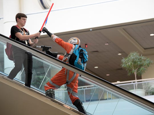 Attendees play-fight while riding an escalator during the Star Wars Celebration event Friday, April 14, 2017 in Orlando, Fla.