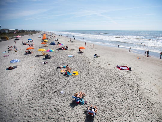 Beach goers lay out on Folly Beach on Wednesday, April