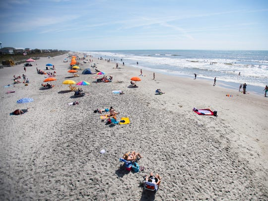 Beach goers lay out on Folly Beach on Wednesday, April 12, 2017.