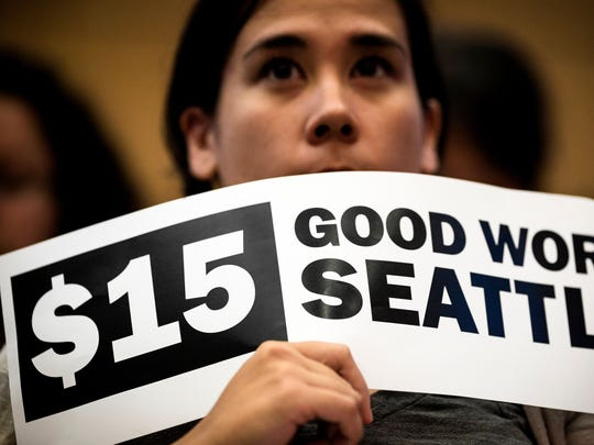 Hoisting signs, supporters showed support for the passage of increasing the minimum wage in the city to $15 for Seattle employers on Monday, June 2, 2014, at City Hall in Seattle. Phased in over the next seven years, Seattle will have one of the highest minimum wages in America.