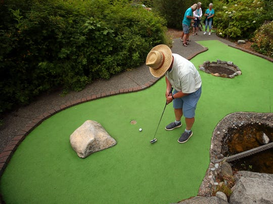 Wendell Crim, 68, of Seabeck, sinks a putt during the mini-golf event at the West Sound Senior Games at NW Golf Range & Timber Falls Mini Golf in Bremerton on Thursday.
